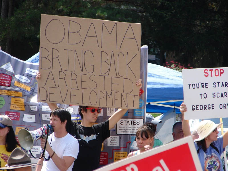Photograph of a Hipster at a Healthcare Town Hall Meeting with a sign that says Obama Bring Back ARRESTED DEVELOPMENT from a somewhat anonymous Flickr user