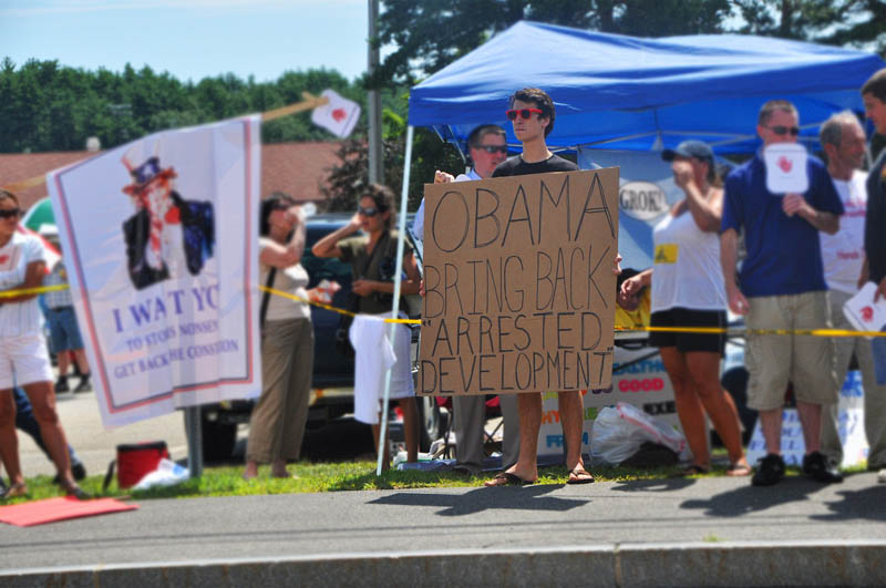 Photograph of a Hipster at a Healthcare Town Hall Meeting with a sign that says Obama Bring Back ARRESTED DEVELOPMENT from Flickr user ccc photography