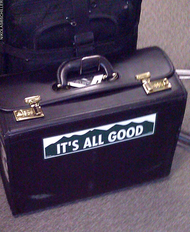 Grainy photograph of a bumper sticker on a briefcase that says It's All Good in a design like the Colorado license plate