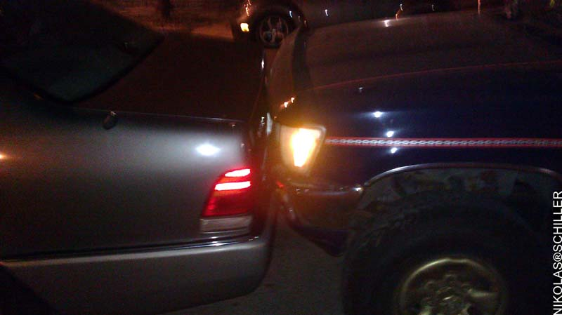 Photograph of a car parked so close to another car they are kissing