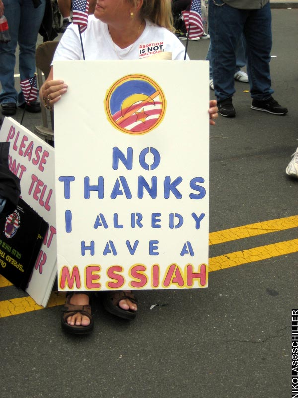 Photograph of a woman holding a sign that says: No thanks, I already have a Messiah