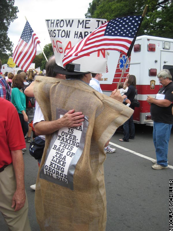 A man dressed as a teabag with the sign that says: Obama is over-taxing this bad of tea like King George III did + a sign that says: Throw me in the Boston Harbor AGAIN