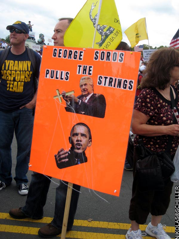 Photograph of a sign that says: George Soros Pulls The Strings