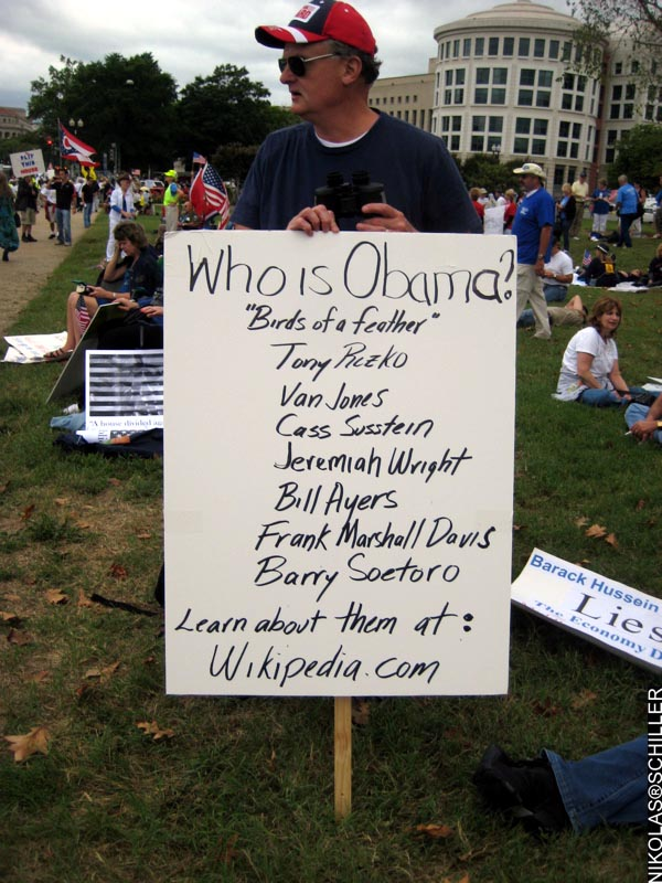 Photograph of a man with sign asking the viewer to do research on Wikipedia.com