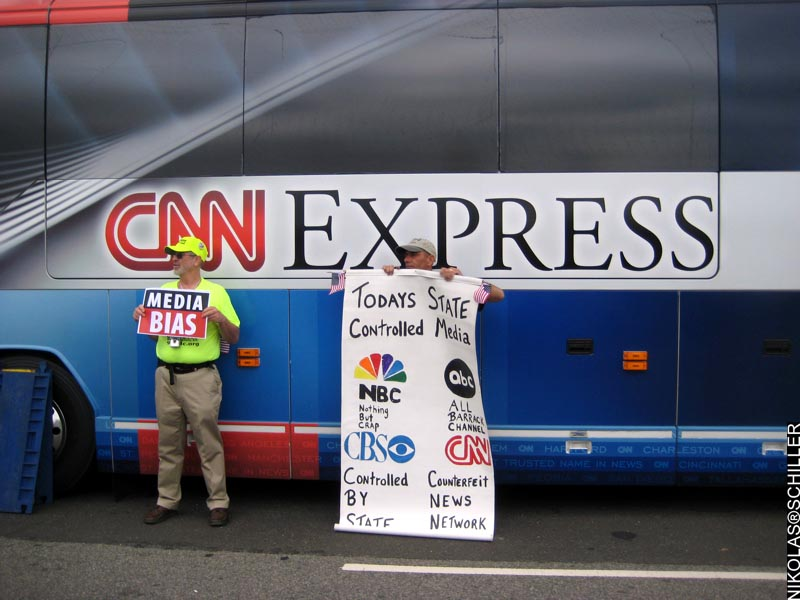 Photograph of people standing outside of the CNN Bus holding signs claiming media bias