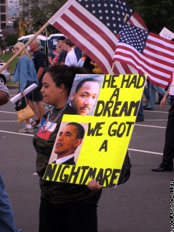 Photograph of a young African American woman holding a sign featuring Martin Luther King and Barack Obama that says: We Had A Dream - We Got A Nightmare